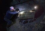Miners move an ore cart inside a mine in Potosi, Bolivia. The mine produces silver and other metals.