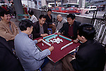 Men playing game of mahjong in outdoor park near busy street in Wanxian, China; city; morning; 042203