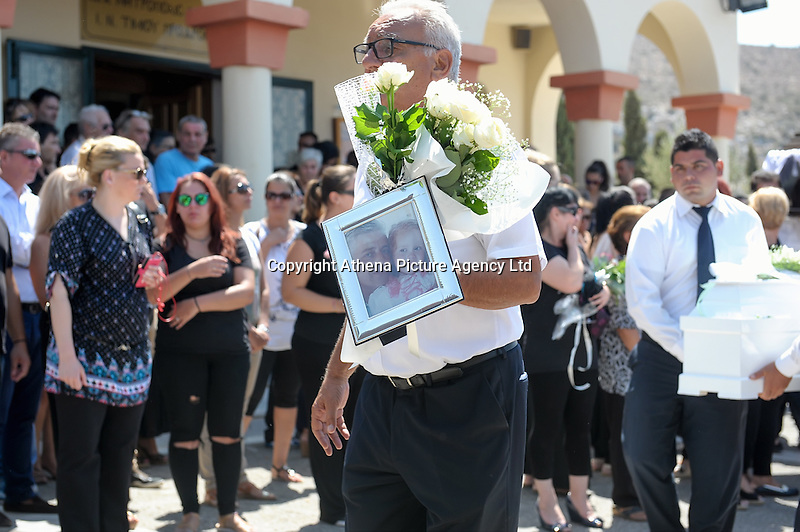 Pictured: A man with a picture and flowers for five year old Sevasti Katife in Schisto, Piraeus, Greece. Friday 19 August 2016<br /> Re: The funeral for Theodosis Katifes and his five year old daughter Sevasti, two of the victims of a crash involving a speed boat and a ltourist boat has taken place at the Schisto area of Piraeus.<br /> Tharsivoulos Lykourezos, the captain of a speedboat that collided with a tourist boat off the Greek island of Aegina, killing four people, has appeared in court.<br /> The speedboat called Duente collided with a tourist boat called Antonia carrying more than 20 people.