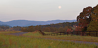 A full moon rises above the mountains and down a winding road during the twilight hours in Albemarle County,VA. Photo/ Andrew Shurtleff
