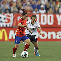 Korea Republic midfielder Lee Sejin (5) dribbles as USWNT midfielder Carli Lloyd (10) defends. In an international friendly, the U.S. Women's National Team (USWNT) (white/blue) defeated Korea Republic (South Korea) (red/blue), 4-1, at Gillette Stadium on June 15, 2013.