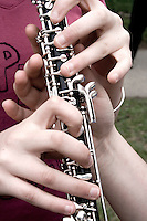 Helping hand tuning up oboe for long parade march. MayDay Parade and Festival. Minneapolis Minnesota USA