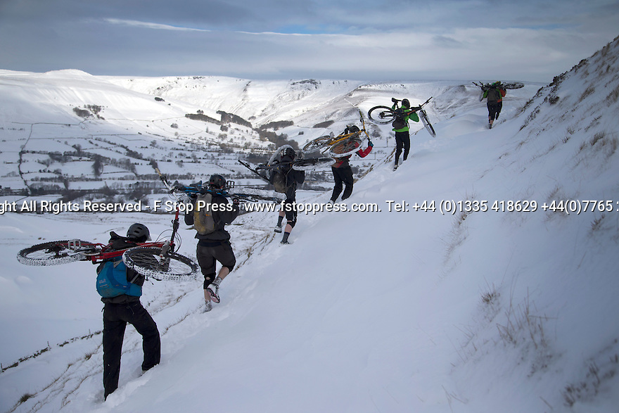01/02/15<br /> <br /> After more overnight snow a group of cyclists carry their mountain bikes around the edge of Mam Tor overlooking the Edale valley in the Derbyshire Peak District.<br /> <br /> All Rights Reserved - F Stop Press.  www.fstoppress.com. Tel: +44 (0)1335 418629 +44(0)7765 242650