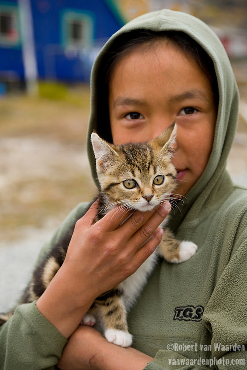 A young girl from Tasiussaq, Greenland,  holds a kitten.