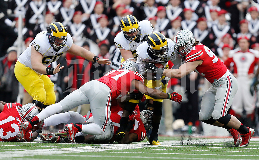 Ohio State Buckeyes linebacker Joshua Perry (37) and Ohio State Buckeyes defensive lineman Joey Bosa (97) tackle Michigan Wolverines quarterback Devin Gardner (98) during the college football game between the Ohio State Buckeyes and the Michigan Wolverines at Ohio Stadium in Columbus, Saturday morning, November 29, 2014. The Ohio State Buckeyes defeated the Michigan Wolverines 42 - 28. (The Columbus Dispatch / Eamon Queeney)