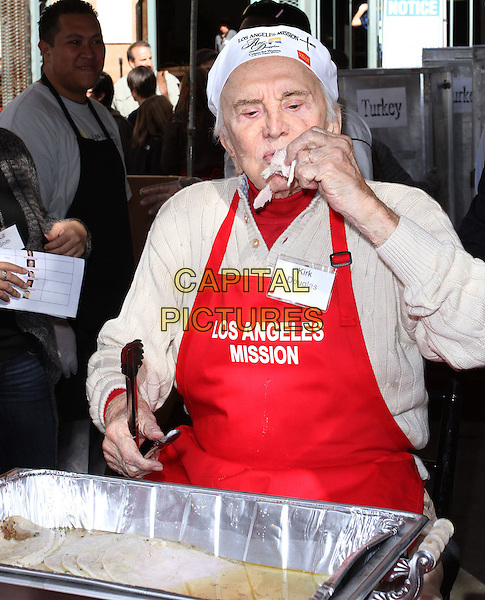 KIRK DOUGLAS .Los Angeles Mission And Anne Douglas Center's Thanksgiving Meal For The Homeless held at The Los Angeles Mission, Los Angeles, CA, USA, .24th November 2010..half length serving food red apron hat beige cardigan turkey .CAP/ADM/KB.©Kevan Brooks/AdMedia/Capital Pictures.