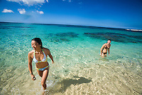 Young women swimming in clear blue water over white sand beach at Mokuleia, North Shore of Oahu