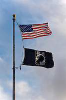United States flag and POW-MIA flag wave from a flag pole.