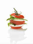 Tomato with vine attached sliced into thirds with mozzarella cheese and fresh basil leaves