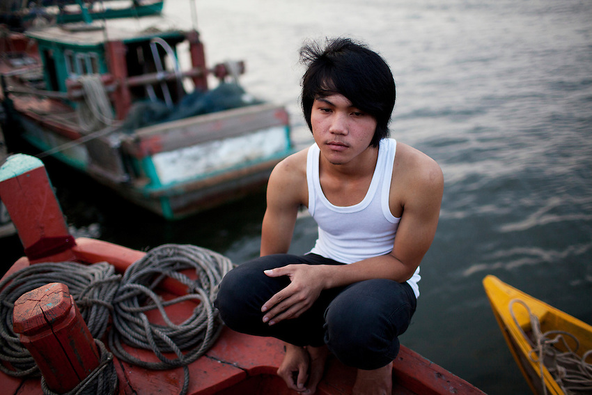 A young Cham muslim fisherman sits on a boat on the Kampong Bay estuary before heading out for a night of fishing in Kampot province, Cambodia, March 10, 2012.
