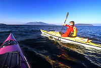 Male paddler in yellow kayak and yellow PFD paddling in San Juan Islands with , Sea Kayaking the San Juan Islands, WA.