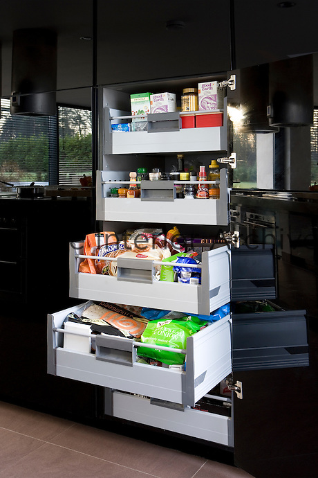 A series of floor-to-ceiling parapan cupboards finished in glossy black conceals ample storage including a set of large drawers for groceries