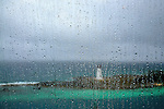 Rain drops on deck window frame a rainy sail away from Nassau