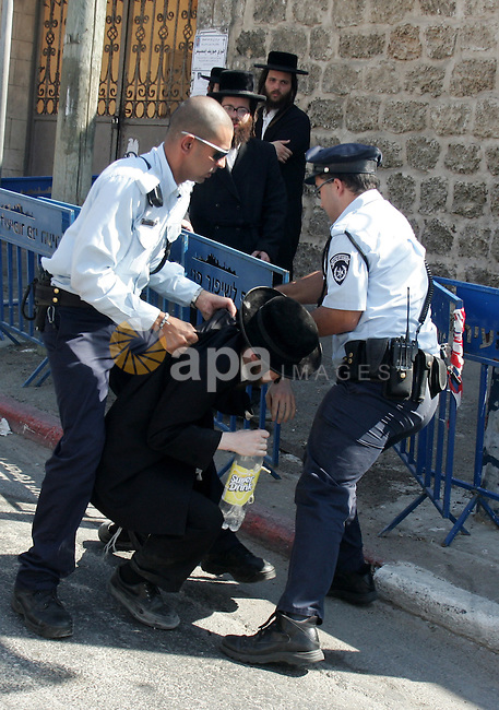 An ultra-Orthodox Jew is grabbed by an Israeli Border policeman during a protest in the coastal town of Jaffa, just south of Tel Aviv, on 31 August 2010 over the town's decision to remove ancient graves found during the construction of a hotel. Photo by Mahfouz Abu Turk