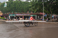 Daytime landscape view of a man driving a tricycle loaded with long poles on Hui Long Jie in Lóngmǎtán Qū of the Lúzhōu Prefecture City in Sichuan Province.  © LAN