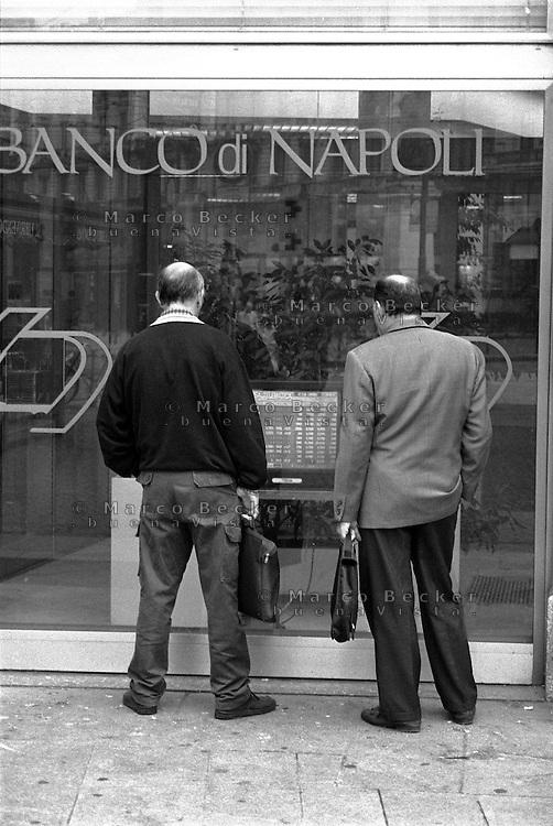 Milano, due uomini con borsa appresso consultano il listino dei titoli finanziari sul monitor di una filiale del Banco di Napoli --- Milan, two men with bag look at the list of financial stocks on the monitor at a Banco di Napoli