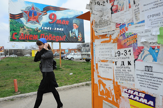 A man walked past a billboard for Victory Day, 9 May, with the portrait of an Ingush war veteran - even though there were mass deportations of Ingush by Stalin in 1944 for allegedly not resisting the Nazi forces - in the centre of Nazran, Ingushetia. April 8, 2010