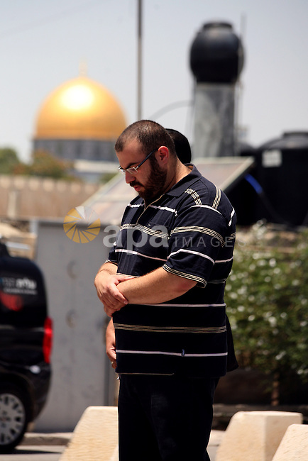 A Palestinian Muslim worshiper attends the Friday prayers in the East Jerusalem neighbourhood of Ras al-Amud after being refused entry into the Al-Aqsa compound in Jerusalem, 30 May 2014. The Israeli police restricted the entrance to the Al-Aqsa mosque and permitted only men over the age of 45 due to intelligence reports of planned disturbances by Palestinians on al-Aqsa compound. Photo by Saeed Qaq