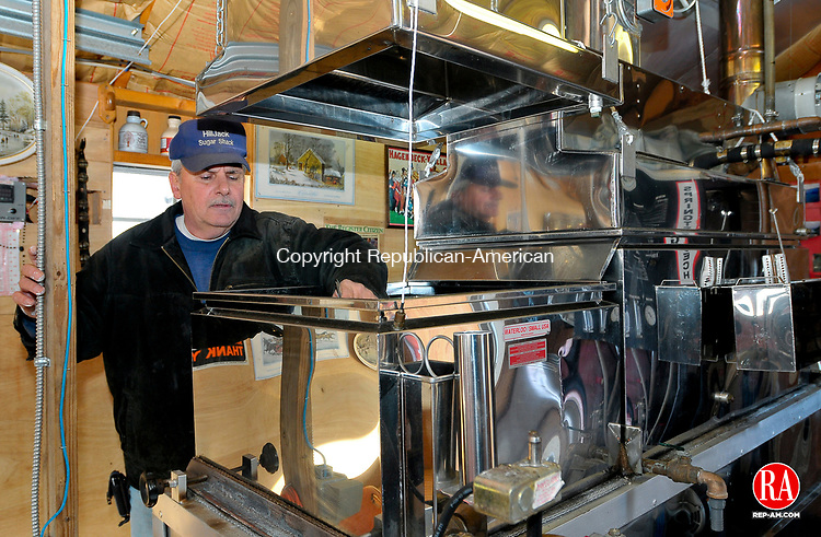 LITCHFIELD, CT-030409JS02-Jim Nivolo, who runs Hilljack Sugar Shack in Litchfield with his son Jesse Nivolo, clear ice from inside the evaporator used for the production of maple syrup on Wednesday. They are in the process of collecting sap and will most likely start cooking this weekend. <br /> This year, the duo put in more that 1200 taps on trees, about 400 more that last year. <br /> Jim Shannon  Republican-American