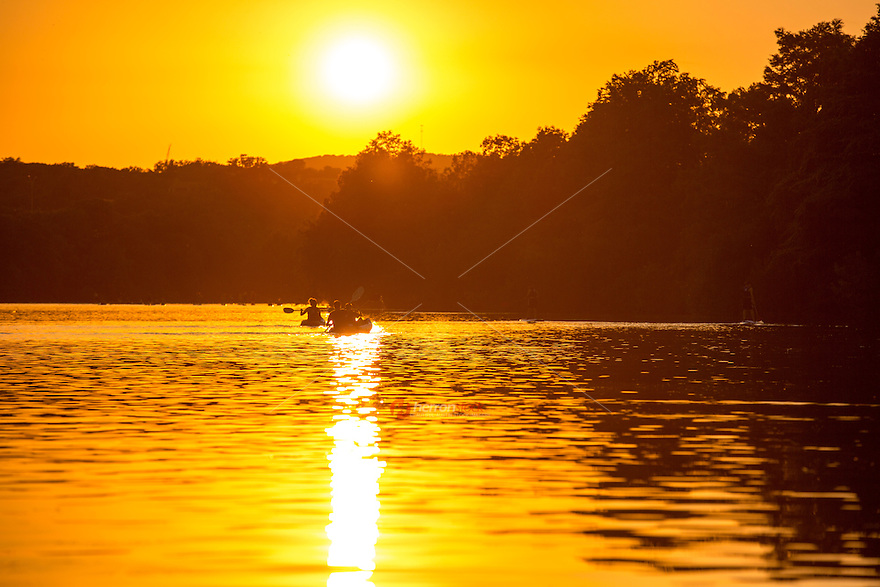 Silhouette of People kayaking and canoeing on Lady Bird Lake during golden Sunset, Austin, Texas.