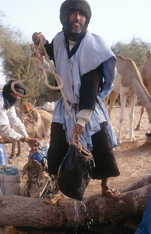 Didi, le chamelier, puisant de l'eau dans le puits de Tenemrerout. Mauritanie. AfriqueDidi, the camel driver drawing water in the Tenemererout well. Mauritania. Africa