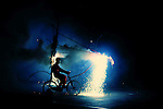 A figure riding a bicycle with fireworks
