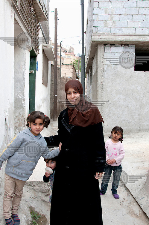 Samah, a 24 year old refugee from Syria, and a couple of her children in the street outside the room she rents. /Felix Features