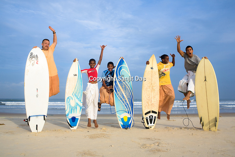 "(Left to Right) Gaura Gopala, Satyaraj, Kirtan Ananda, Dicky and Daruka Dasa, the Krishna devotees of the Kaliya Mardana Krishna Ashram pose for a portrait at the beach before they head out for a surf on Arabian Sea in Mangalore beach, Karnataka, India.  ..Krishna devotees in the Gaudiya Vaishnava tradition of Hinduism, they are known collectively as the ""surfing swamis."" The ""surfing ashram"" is growing in popularity and surfing here is a form of meditation, a spiritual practice leading to heightened states of awareness."