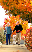 A couple walks a dog in Asheville NC's Biltmore Park Town Square, a planned community in the Blue Ridge Mountains of residential living, office spaces and shopping.