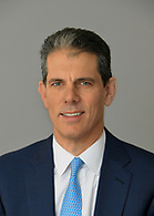 A corporate headshot with a gray background.