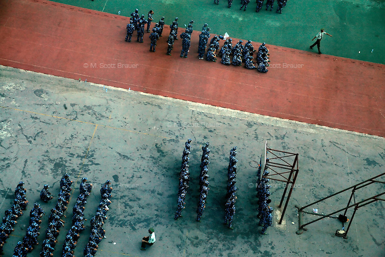 Freshmen at the Nanjing University of Traditional Chinese Medicine line up for military indocrination training on a basketball court in Nanjing, China.