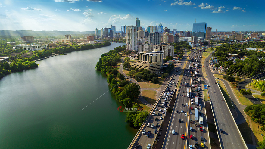 Sunrays paint the Austin Skyline as rush hour traffic picks up on I-35. In the heart of Austin is the Ann and Roy Butler Hike-and-Bike Trail at Lady Bird Lake, a lush, urban path that meanders along the water's edge and passes by skyscrapers, neighborhoods, ball fields and cultural attractions.