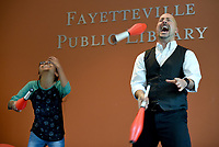 NWA Democrat-Gazette/DAVID GOTTSCHALK Victoria Silva, 11, with My Other Mother summer camp, assists Wednesday, July 3, 2019, Jeff Koziatek during the Juggling Jeff Comedy Show at the Fayetteville Public Library. Juggling Jeff performed two shows that featured comedy, audience interaction and juggling a variety of items that included diapers.