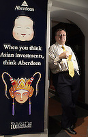 26-SEP-02: HUGH YOUNG: SINGAPORE<br /> Hugh Young of Aberdeen Asset Management leans against a wall outside his office in Singapore that displays a poster celebrating 10 years of the company's presence in Singapore.<br /> Photo by Munshi Ahmed/sinopix<br /> ©sinopix