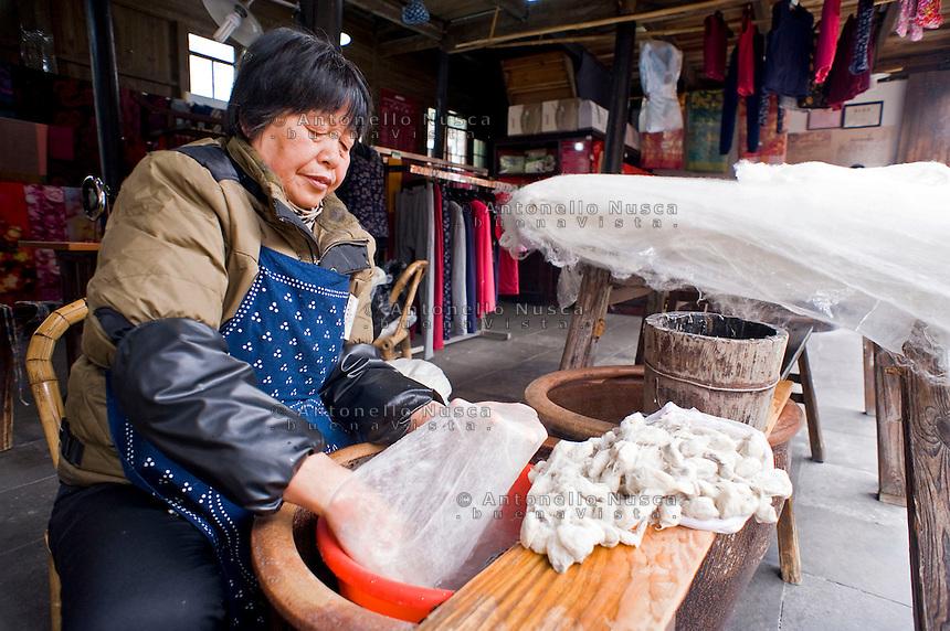 Wuzhen, Cina. Una donna lavora il bozzolo del baco per poi lavorare con  la seta.<br /> A woman during the old process to produce silk by the cocoon in Wuzhen