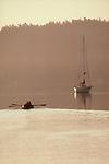San Juan Islands, Boaters rowing to anchored sailboat, Friday harbor, San juan Island, Washington State, Pacific Northwest, USA,