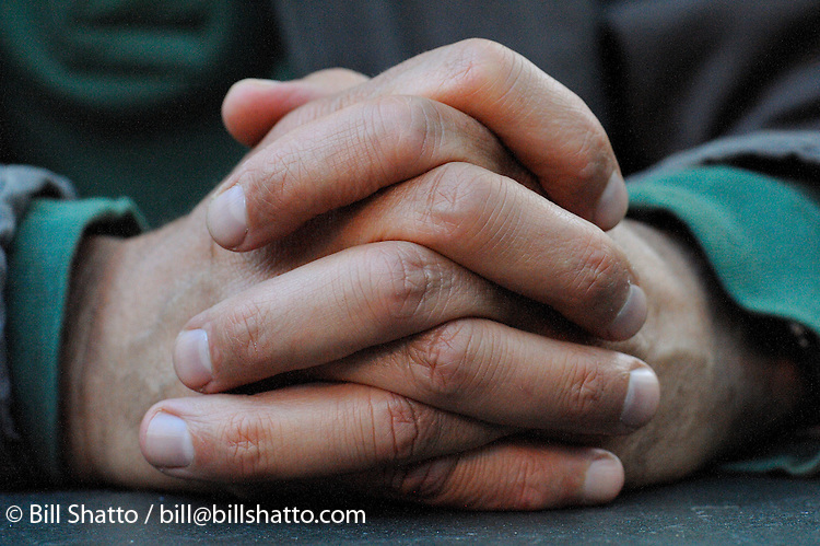 A man's folded hands.