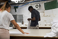 Allan Baxter, 40, (right) and Stela Poparova, 24, work in the laundry of the Harborside Inn in Edgartown, Martha's Vineyard, Massachusetts, USA. From St. Mary Parish, Jamaica, Baxter has worked at the hotel on an H2B visa for seasonal foreign workers. He spent last winter working in Stowe, Vermont, as well. The hotel has had difficulty this year getting as many H2B visas as it had in previous years. As a result, Baxter is the only person working in the laundry room on most days; it was a two-person job last year. Workers from other areas of the hotel, like Poparova, who is officially employed as a pool attendant, sometimes work short shifts in the laundry room to help Baxter. Poparova is from Plovdiv, Bulgaria, and has a J1 visa for students. She is a linguisitics student at New Bulgarian University in Sofia, Bulgaria.
