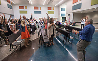 NWA Democrat-Gazette/BEN GOFF @NWABENGOFF<br /> Kenny Timbrel, right, Osage Creek Elementary music teacher, leads attendees in the school's 'Alma Otter' song (the school's mascot is an otter) Friday, Aug. 11, 2017, during a grand opening for Osage Creek Elementary School and Creekside Middle School in Bentonville. The new schools will welcome their first students Monday.