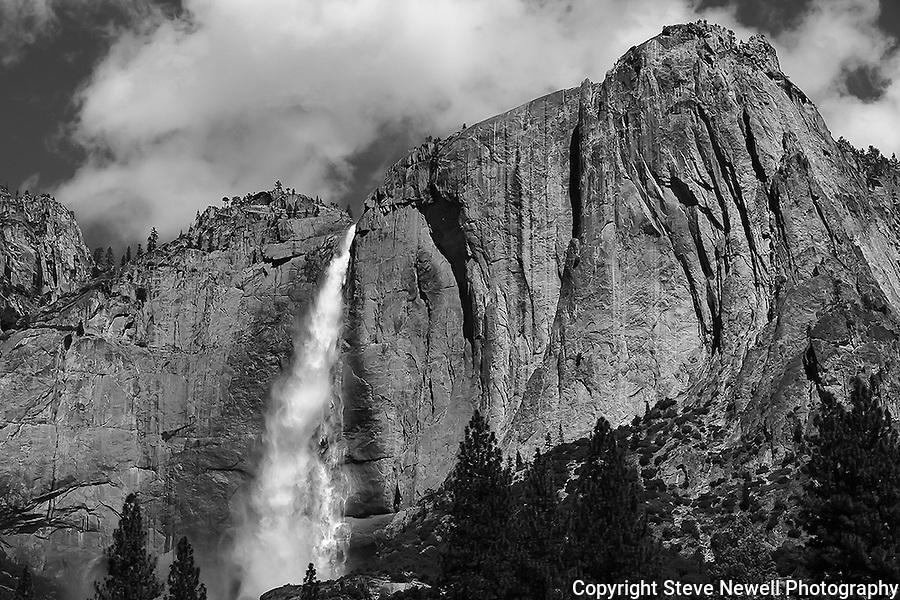 """Yosemite Falls Waterfall 7"" monochrome artistic Yosemite Falls Waterfall, Yosemite National Park, California.This is a monochrome photo that I made an adjustment to the texture of the rock and trees to give it more of an artistic perspective. I spent two weeks in the Spring of 2013 climbing up the opposite canyon's wall in order to get an angle that captured all three sections of the waterfall. I learned on the Yosemite National Park's website that no one had a photograph of the middle section of the waterfall.  Their description of the middle section is ""often ignored middle section""  All other photographers only have photographs showing an angle that has the upper and lower sections in view.  I had to climb down and return moving further up the canyon to get an angle to see directly into the middle section."