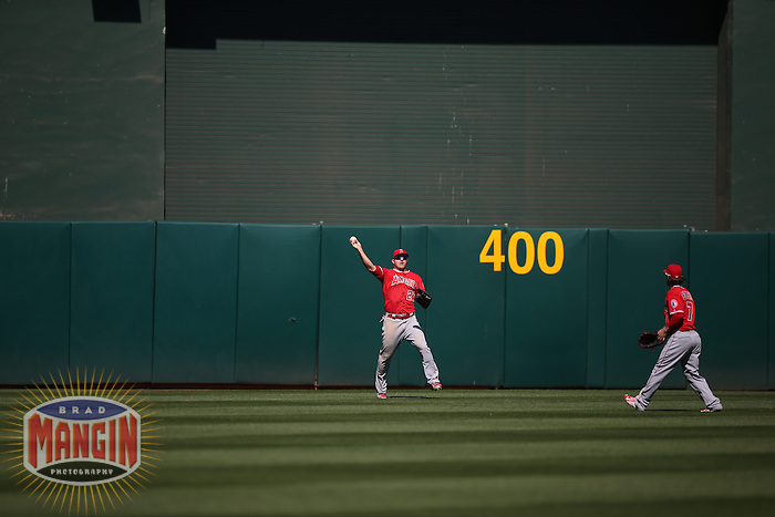 OAKLAND, CA - APRIL 30:  Mike Trout #27 of the Los Angeles Angels shows the ball after making a leaping catch in centerfield with two outs in the bottom of the 9th inning on a fly ball off the bat of Oakland Athletics batter Ike Davis #17 at O.co Coliseum on Thursday, April 30, 2015 in Oakland, California. The catch came with the bases loaded and saved the game for the Angels who won by a final score of 6-5. Photo by Brad Mangin