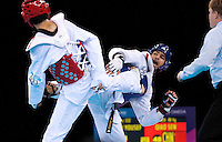 04 DEC 2011 - LONDON, GBR - Yousef Karami (IRI) (in blue, on right) tries to strike Sen Qiao (CHN) during their men's -80kg category  preliminary round contest at the London International Taekwondo Invitational and 2012 Olympic Games test event at the ExCel Exhibition Centre in London, Great Britain .(PHOTO (C) NIGEL FARROW)