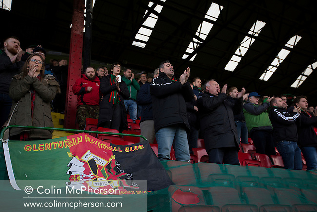 Home supporters in the main stand applauding their team from the pitch at The Oval, Belfast after Glentoran hosted city-rivals Cliftonville in an NIFL Premiership match. Glentoran, formed in 1892, have been based at The Oval since their formation and are historically one of Northern Ireland's 'big two' football clubs. They had an unprecendentally bad start to the 2016-17 league campaign, but came from behind to win this fixture 2-1, watched by a crowd of 1872.