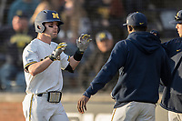 Michigan Wolverines shortstop Michael Brdar (9) is greeted by his teammates after driving in a run with a sacrifice fly against the Michigan State Spartans during the NCAA baseball game on April 18, 2017 at Ray Fisher Stadium in Ann Arbor, Michigan. Michigan defeated Michigan State 12-4. (Andrew Woolley/Four Seam Images)