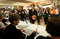 DENVER, CO--A young fan watches coach Amy Tucker sign posters during a fan autograph session at the Pepsi Center for the 2012 NCAA Women's Final Four festivities in Denver, CO.