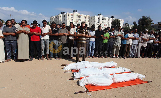 Palestinians pray next to the bodies of three members of Abu Hadaf family, whom medics said were killed by an Israeli air strike, during their funeral in Khan Younis in the southern Gaza Strip August 9, 2014. Israel launched more than 20 aerial attacks in Gaza early on Saturday and militants fired several rockets at Israel in a second day of violence since a failure to extend an Egyptian-mediated truce that halted a monthlong war earlier this week. The Israeli military said that since midnight it had attacked more than 20 sites in the coastal enclave where Hamas Islamists are dominant, without specifying the targets. Medical officials in Gaza said two Palestinians were killed when their motorcycle was bombed and the bodies of three others were found beneath the rubble of one of three bombed mosques. The air strikes which lasted through the night also bombed three houses, and fighter planes also strafed open areas, medical officials said. Photo by Ramadan El-Agha