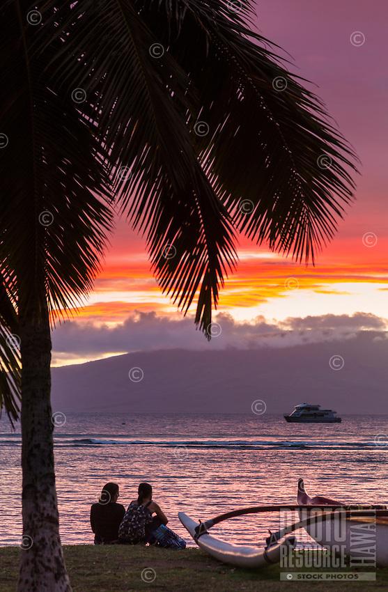 Tourists on a Maui beach watch the sun set behind Lana'i.