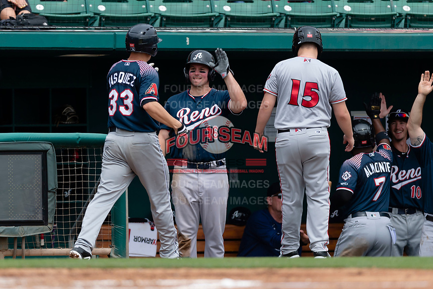 Reno Aces Travis Snider (16) congratulates Anthony Vasquez (33) after scoring a run during a game against the Fresno Grizzlies at Chukchansi Park on April 8, 2019 in Fresno, California. Fresno defeated Reno 7-6. (Zachary Lucy/Four Seam Images)