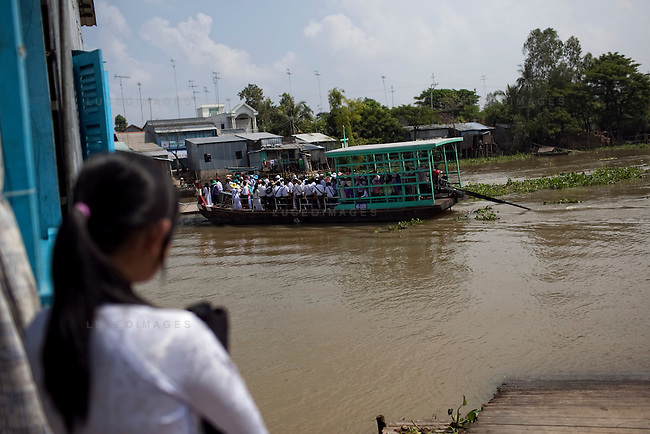 "A school girl watches as her classmates cross the Hau Giang River, a tributary of the Mekong River, in Long Xuyen, the capital of An Giang Province, Vietnam. She was late from school and missed they ferry. When the Mekong River reaches Vietnam it splits into two smaller riveres. The ""Tien Giang"", which means ""upper river"" and the ""Hau Giang"", which means ""lower river"". Photo taken on Monday, December 8, 2009. Kevin German / Luceo Images"