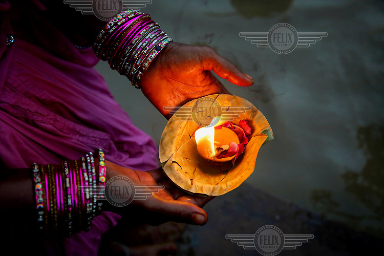 A devotee carries a candle burning in a leaf holder.
